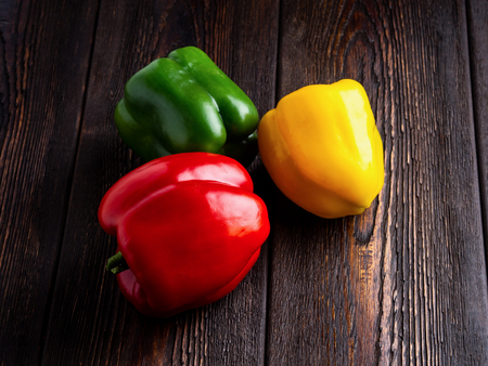 green, yellow and red bell peppers on dark brown wooden background. Well suited for the catalog. Standard-Bild - 117117712