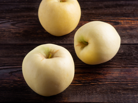 Yellow apples on dark brown wooden background. Well suited for the catalog. Standard-Bild - 117117719