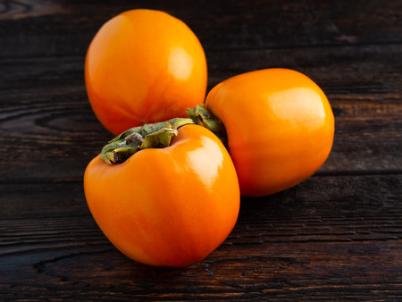 persimmon on dark brown wooden background. Well suited for the catalog. Standard-Bild - 117117722