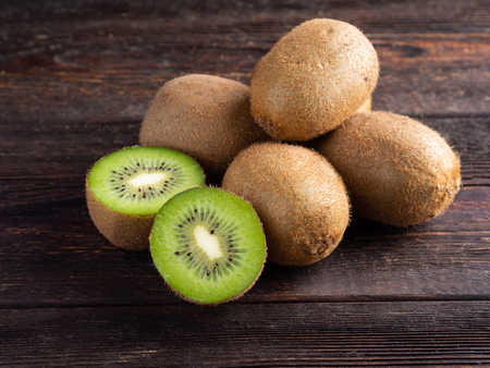 Kiwi on dark brown wooden background. Well suited for the catalog. Standard-Bild - 117117726