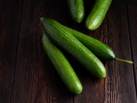 cucumbers on dark brown wooden background. Well suited for the catalog. Standard-Bild - 117117727