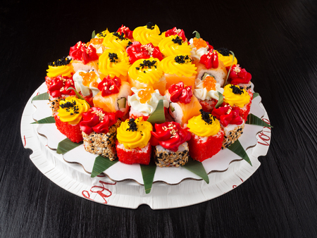 Sushi (rolls) cake on a black wooden background Standard-Bild - 122315697