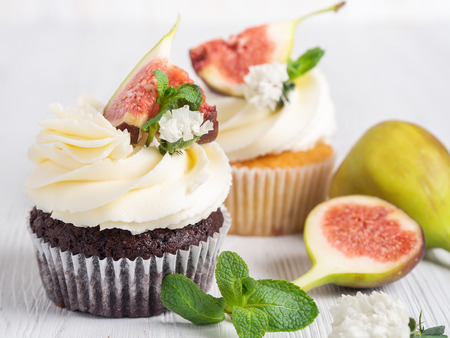 Chocolate muffin with figs on a white wooden background. Close up