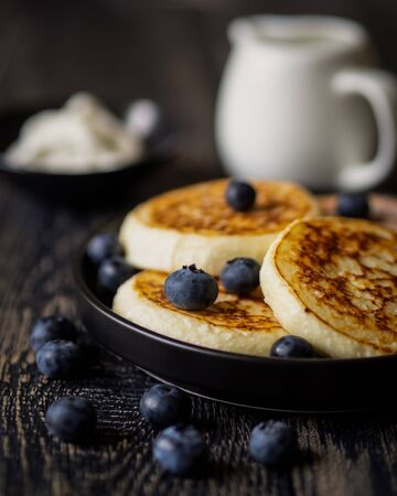 Pancakes (cheese cakes, cottage cheese) with blueberries on a dark wooden table Standard-Bild - 131069868