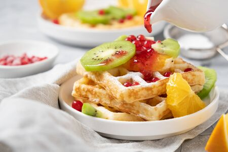 Waffles with berries, fruits, powdered sugar and berry syrup. Standard-Bild