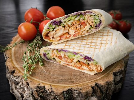 Tasty juicy shawarma in a cut. Near a branch of tomatoes and thyme.