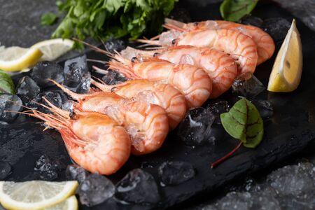 Bright juicy prawns on ice with lemon, green leaves. Standard-Bild
