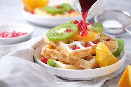 delicate waffles with fruits and berries and fruit syrup