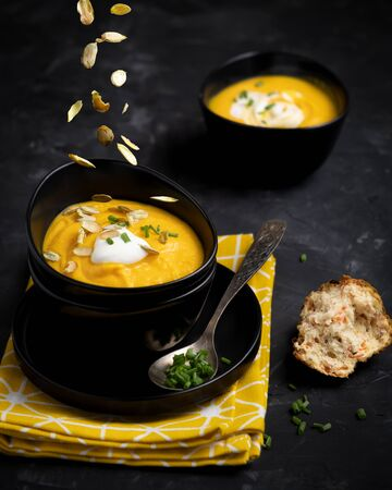 Pumpkin soup with sour cream, herbs and pumpkin seeds. Soup in black bowls on a dark background with a bright yellow towel. Vertical photo. Standard-Bild