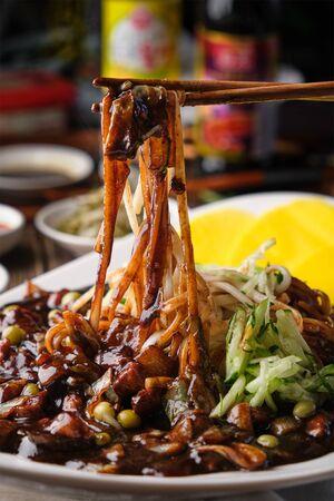 Korean noodles with dark bean sauce on a chopstick. Vertical.