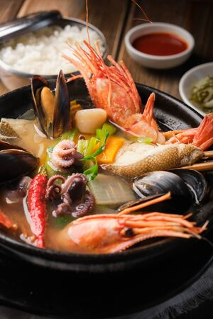 Korean sea soup (hemultan) with halibut, shrimp, mussels and young octopuses. Vertical
