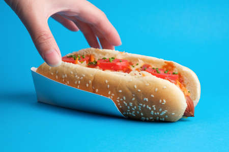 A hand reaches for a delicious juicy hot dog. Bright blue background