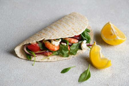 Quesadillas with shrimps on a light concrete background. Lemon, herbs.