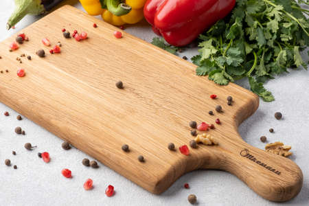 Scattered pepper on a light background. Chopping board, herbs, vegetables. Copy space, blank.