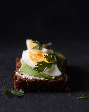 Rye bread appetizer with curd cheese, egg and avocado on black background. Vertical photo. Standard-Bild
