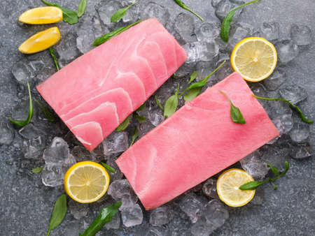Fresh tuna fillet on ice with lemon and basil. View from above. Tin background.