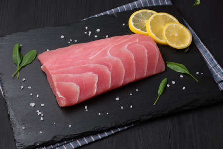 Fresh tuna fillet on a stone plate. Black background.