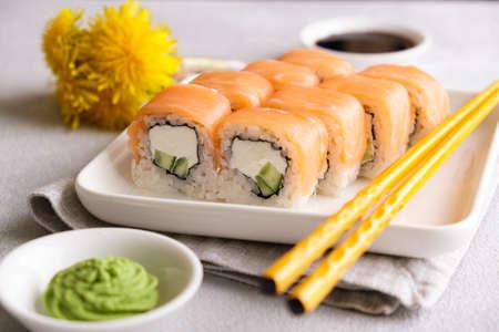 Philadelphia rolls on a white plate, yellow chopsticks.