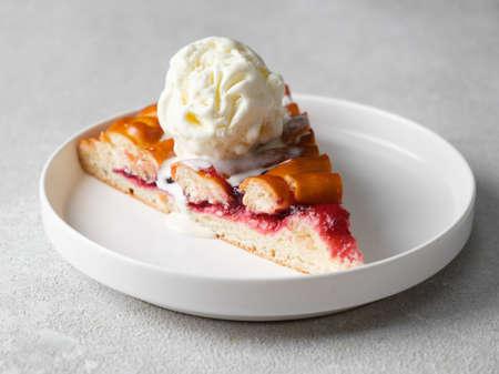 Piece of raspberry pie with ice cream on a light background Standard-Bild