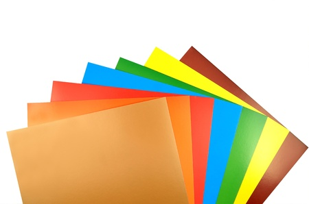 sheets of color paper are spread out around