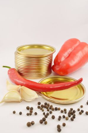 Sweet and sharp pepper, fragrant pepper, garlic and metal covers for cans on the isolated white background Stock Photo