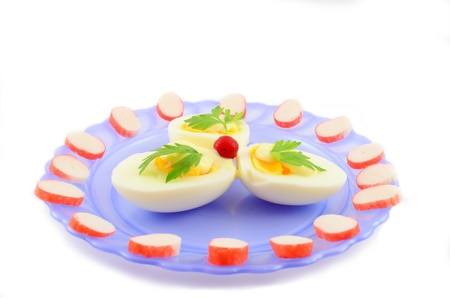 Cooked boiled eggs with sauce, decorated with parsley, cranberries and crab sticks