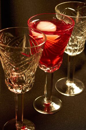 Empty crystal glasses and a glass of red wine with ice