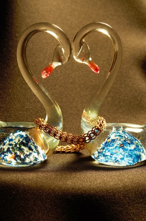 Figurine glass swans with a bright blue pattern,related gold chain on a black background