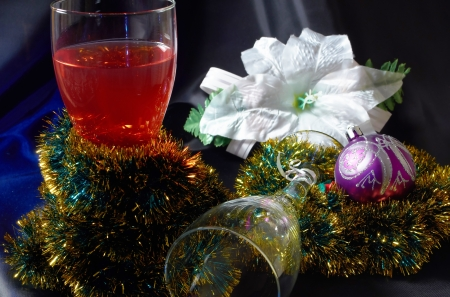 Wineglass and white artificial flower decorated lights and Christmas ball on a black background