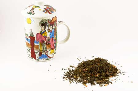 A handful of green leaf tea with jasmine and a mug for tea