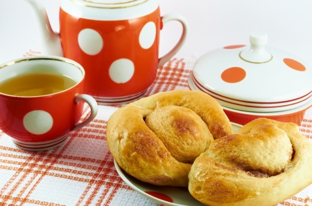rubicund: Rubicund delicious homemade cakes on a plate and cup of tea on a background of tea set Stock Photo