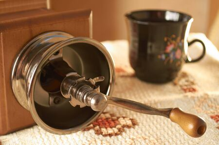 Manual coffee grinder and ceramic cup on woven tablecloth