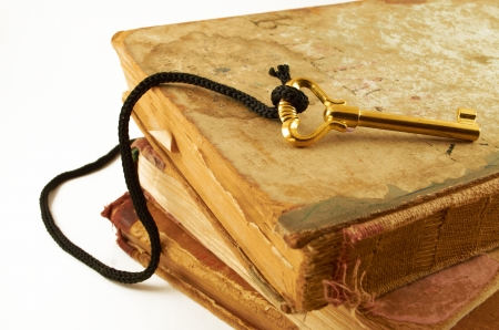 Golden key on old books isolated on white background Stock Photo