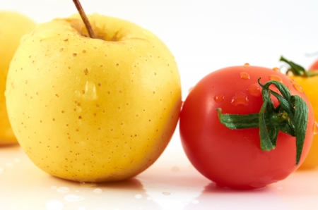Juicy apples and tomato in drops of water on a white background Stock Photo
