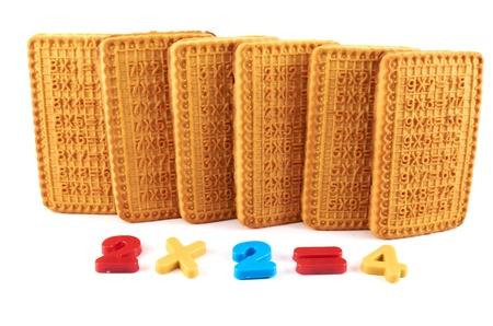 multiplicacion: Galletas de torta dulce y de plástico cifras sobre un fondo blanco