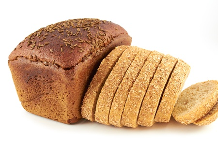 A loaf of rye bread topped with coriander seeds and sliced wheat bread with bran