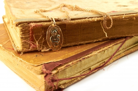 Gold chain  with pendant  of the Virgin on a background of old battered books