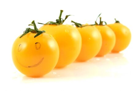 Juicy ripe yellow tomato  in drops of water on a white background