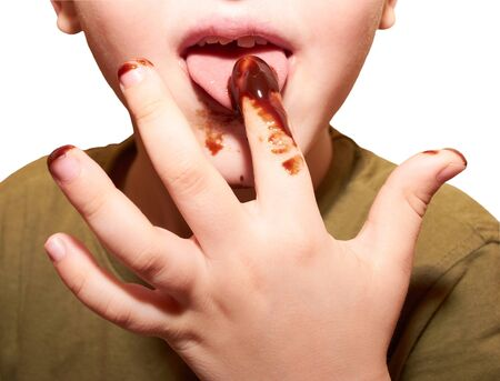 Child licks a chocolate glaze with your finger Stock Photo - 18054682