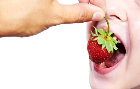 Child eats strawberry with adult hands