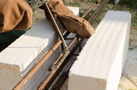 Welder performs welding fixtures on a construction site