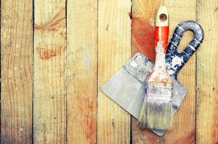 Trowel and paint brush on the wooden background