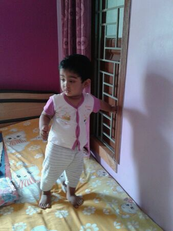 babyhood: A child stands on bed in his bedroom