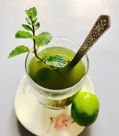herbolario: A glass of peppermint juice and a bunch of peppermint plants with lemon