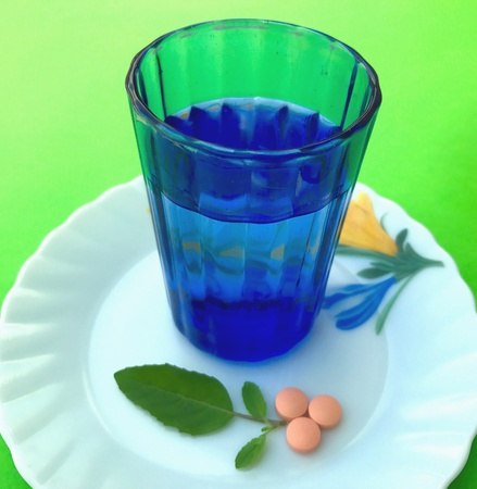 Green leaves, herbal tablets and a glass of water in the plate