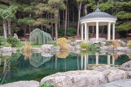 rotunda: Antique gazebo in a park near a pond in high quality Stock Photo