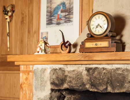 warm things: Vintage wooden clock and a tobacco pipe on a stand on the mantelpiece  in high quality Stock Photo