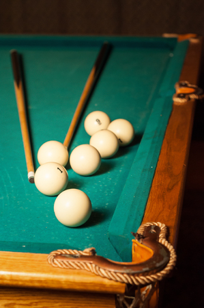 billiard cue and balls on a green table in high quality