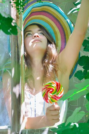 sweettooth: funny girl wearing a colorful hat with lollipop in a window with grape leaves in high quality Stock Photo