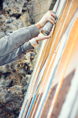 Boy painting graffiti close-up in high quality
